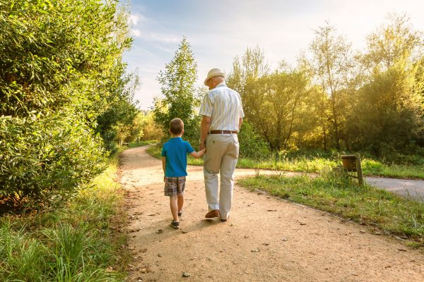 grandpa walking with grandson down a dirt road