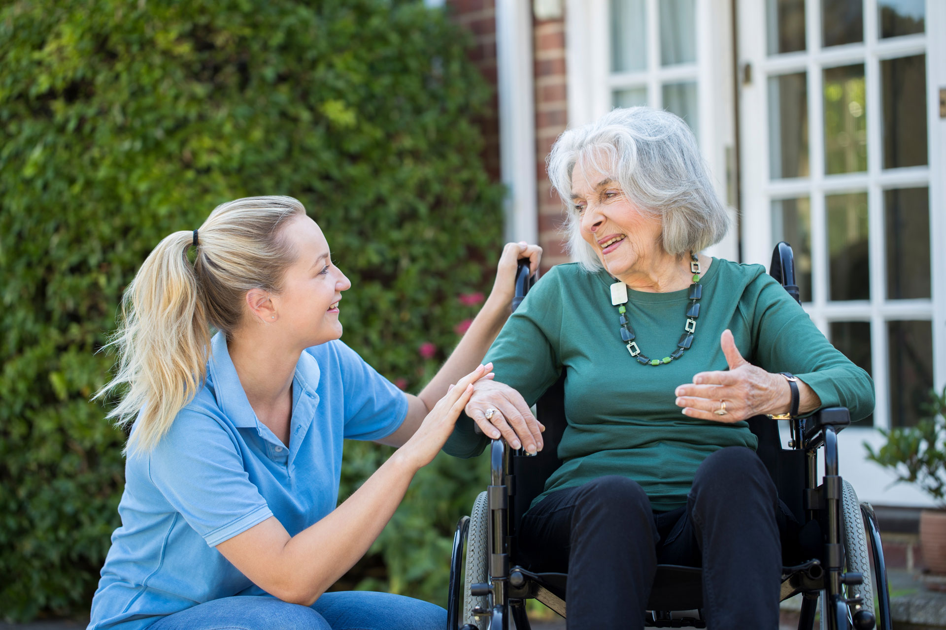 Senior woman, sitting in wheelchair outside, visiting with a woman