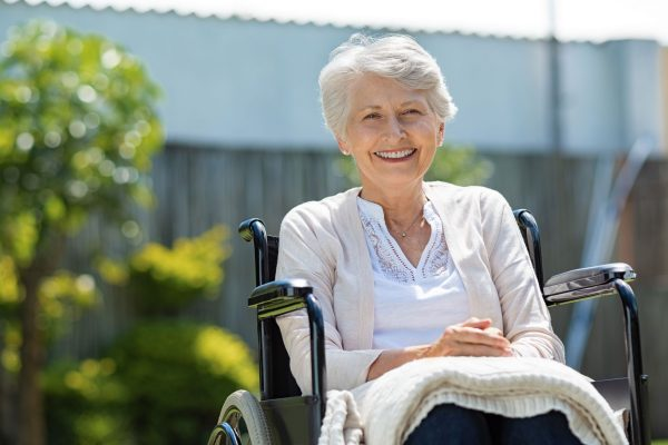 senior woman sitting outdoors in wheelchair, smiling, enjoying the afternoon