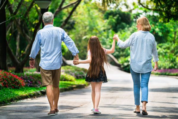 grandparents walking on a pathway with their granddaughter, holding hands and swinging hands as they walk