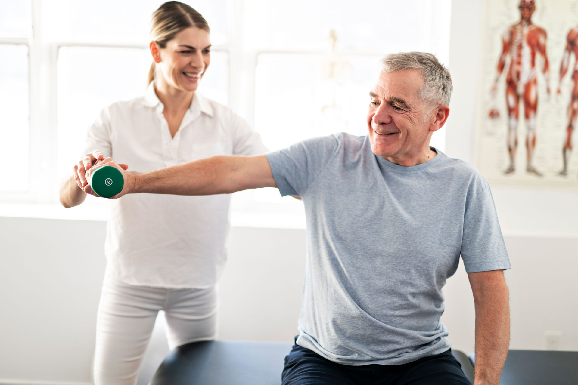 senior man working on physical therapy exercises with woman supervising