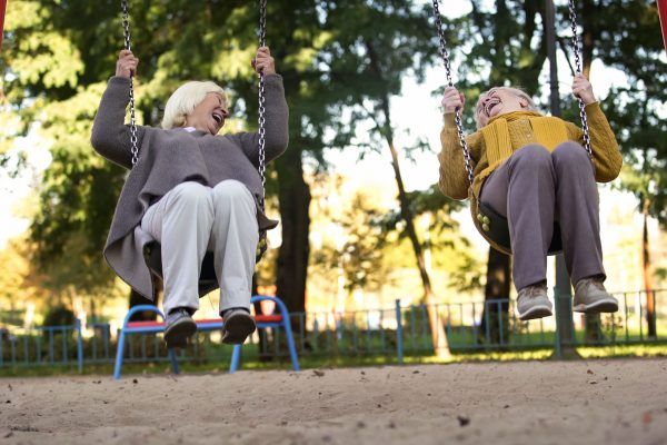 two women swinging on swings at a playground, laughing.