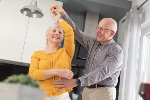 husband and wife, dancing in their kitchen, smiling and enjoying one another's company