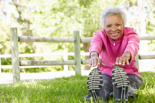 active senior, stretching while seated in the grass, getting ready to exercise. She is wearing a pink sweatshirt and is smiling.
