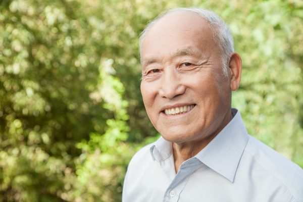 Senior man smiling with green trees in the background