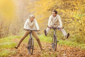 A man and woman riding bikes in the fall, kicking their legs out off the pedals, laughing and having fun!