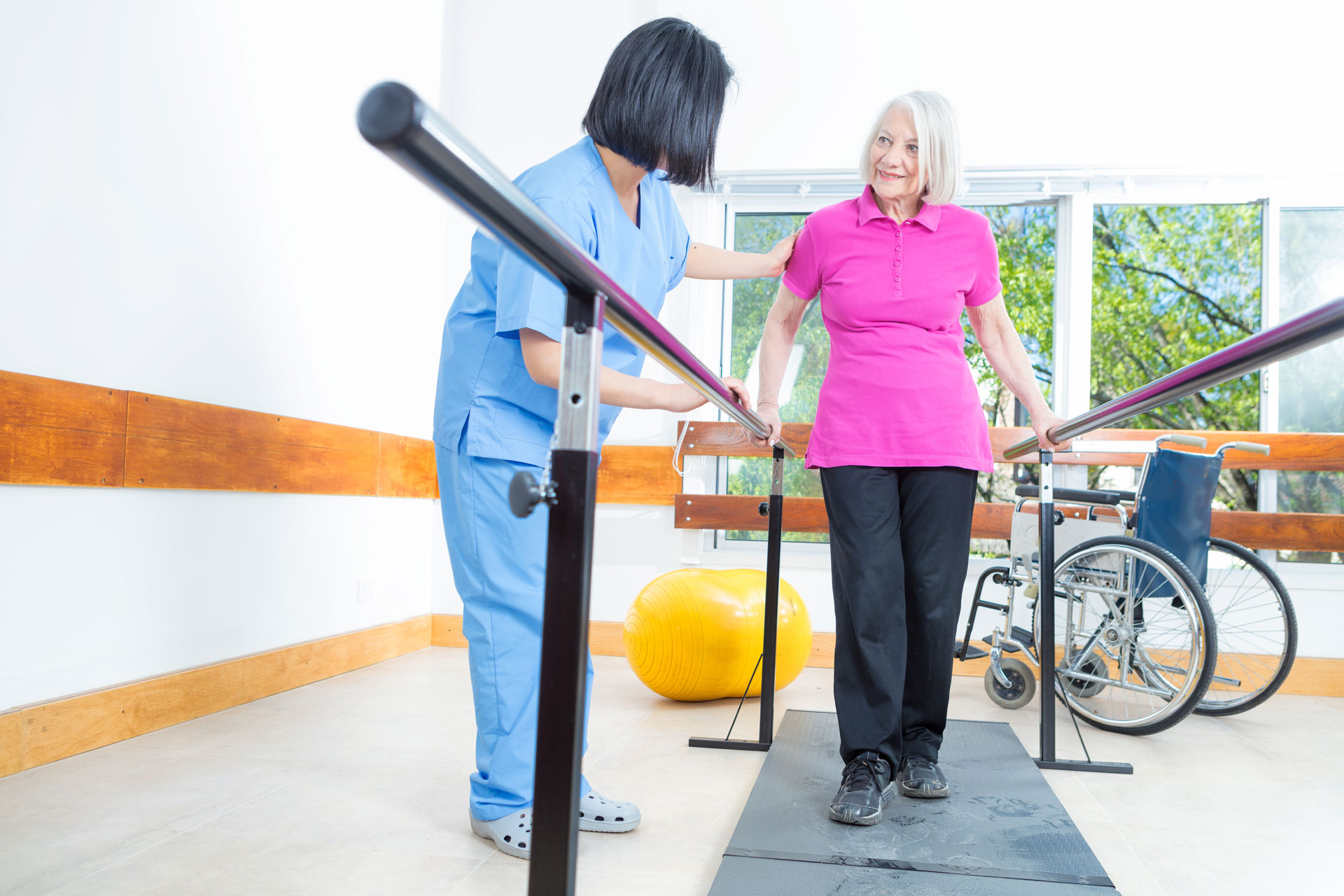 senior woman doing rehabilitation therapy exercises with a physical therapist