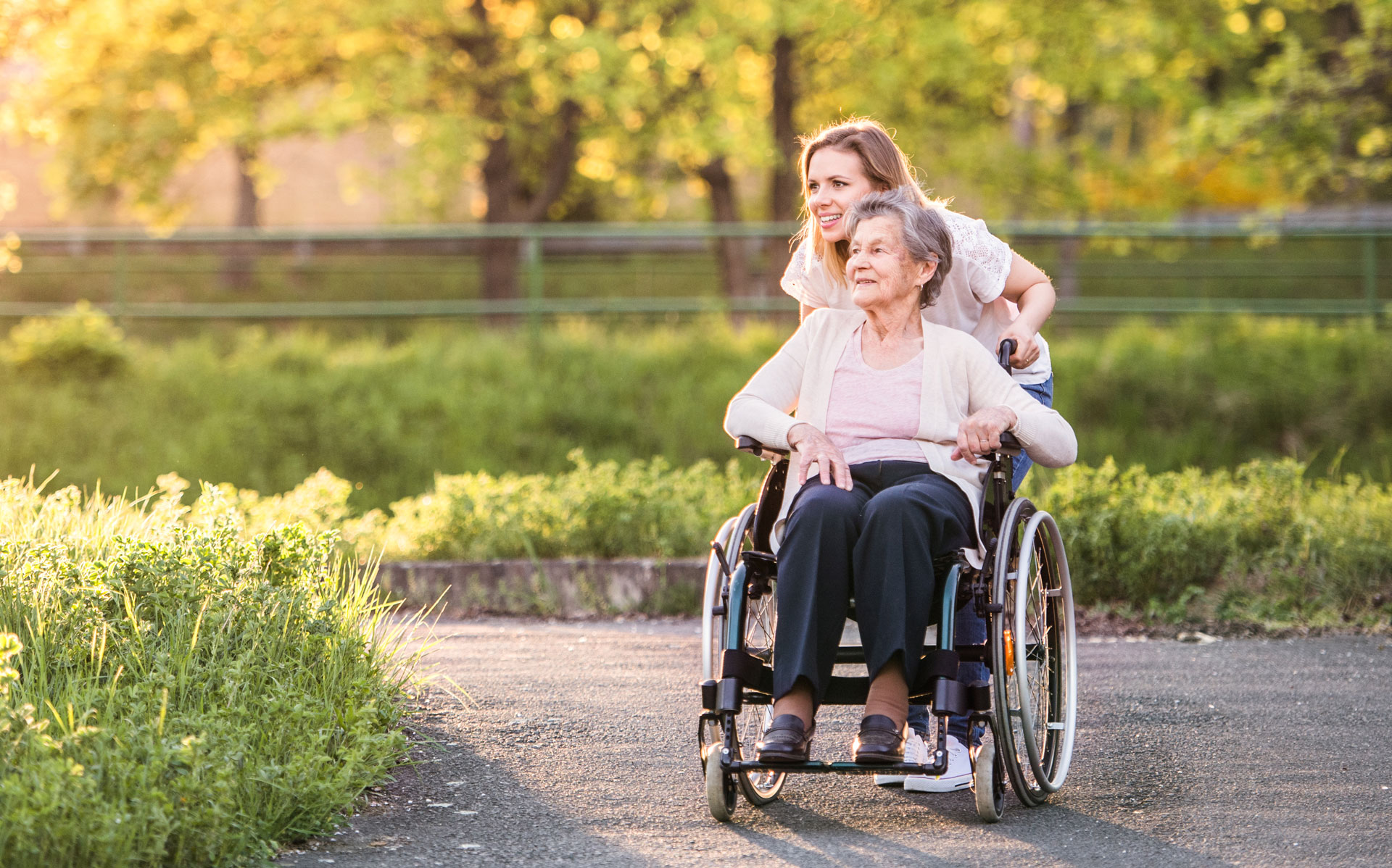 senior woman being pushed outdoors in her wheelchair by a woman, enjoying the scenery